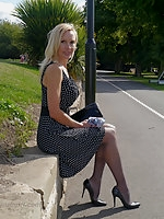 Monica, is outdoors in a lovely dress with sharp pointy high heel shoes